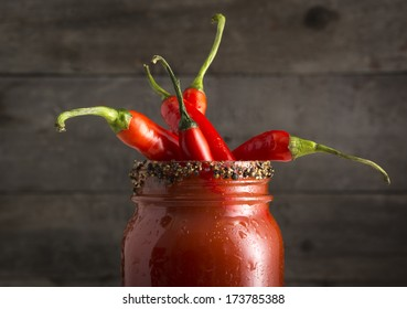 Closeup of Bloody Mary or Bloody Ceasar cocktail in mason jar rimmed with black pepper and filled with red jalapeno peppers