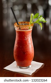 closeup of a bloody mary cocktail garnished with a celery sick isolated on a busy bar top