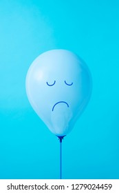 closeup of a blue balloon with a sad face drawn in it, on a blue background, with some blank space on top