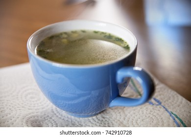 Close-up of a blue cup of hot soup on a paper napkin