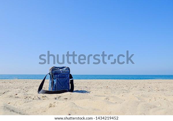 Blue denim bag with black strap on sandy beach against blue sky