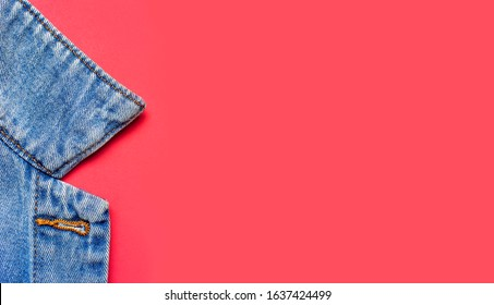 Close-up Blue denim jacket on pink background top view flat lay copy space. Denim, fashionable jacket, women's or men's trend clothing, fashion background. Denim texture