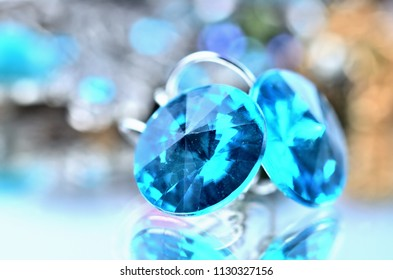 Close-up of blue earrings jewels - reflection effect - colored backgrounds