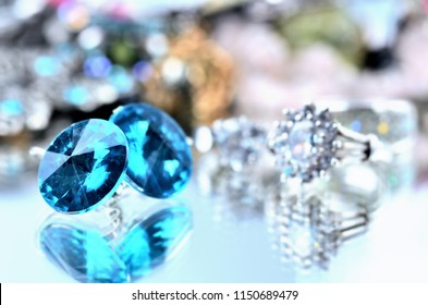 Close-up of blue earrings jewels - reflection effect - colored backgrounds with silver ring