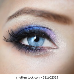 close-up  blue eye of a beautiful sexy young  with lilac and pink hair  eyelash makeup and shadows