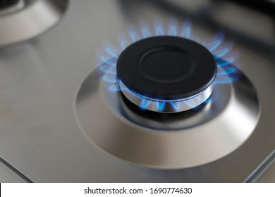 Closeup blue flame from a gas stove burner. Stainless steel kitchen surface.