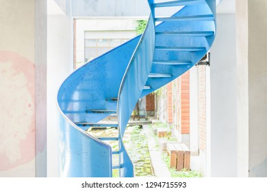 close-up of blue metal spiral ladder going up in daylight