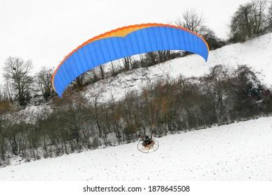 paramoteur bleu en gros plan survolant des champs de neige en Ile-de-France