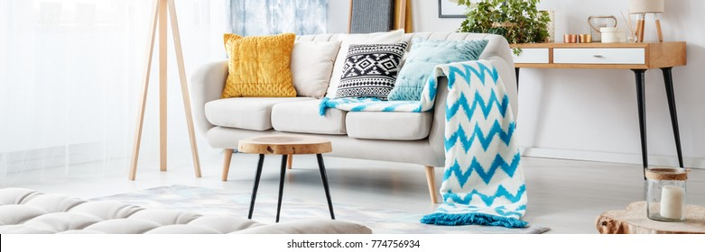 Close-up of blue patterned blanket on sofa with gold pillow in living room with wooden stool
