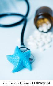closeup of a blue plastic starfish and some pills on a doctors desk, in a doctors office, depicting the medical assistance in summer