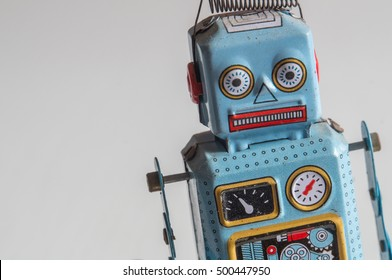 Closeup of a blue and red tin robot toy's upper torso and head, facing front, standing on the rIght of the picture, on a blurred gradient background.
