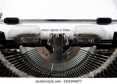 """closeup of a blue retro typewriter ,Words """"Once upon a Time"""" written with old typewriter on white paper in vintage style"""