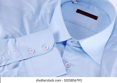 Close-up of a blue shirt with a light buttons and red fashion label