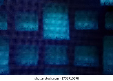 Close-up of a blue textured plastic sheet, backlit through a wall of hollow tiles to form a pattern of irregular squares and rectangles