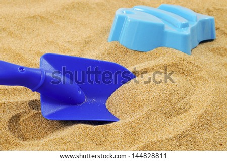 closeup of a blue toy shovel and a blue fish-shaped mold on the sand