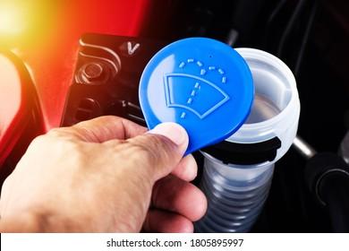 Closeup blue windshield washer fluid reservoir cap in engine room.