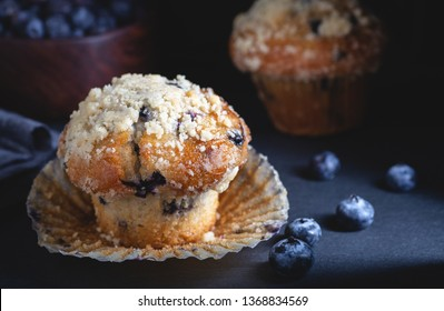 Closeup of a blueberry muffin with a bowl of blueberries and muffin in a dark background