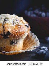 Closeup of a blueberry muffin with a bowl of blueberries in a dark background