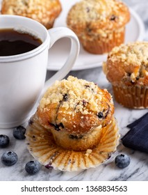 Closeup of a blueberry muffin with a cup of coffee and blueberries on a marble surface with muffins in background