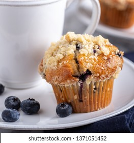 Closeup of a blueberry muffin with a cup of coffee and blueberries on a plate