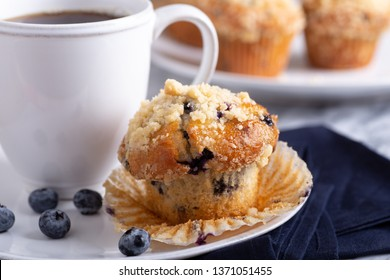 Closeup of a blueberry muffin with a cup of coffee and blueberries on a plate with muffins in background