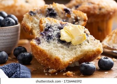 Closeup of a blueberry muffin cut in half with butter and fresh berries on a rustic wooden cutting board