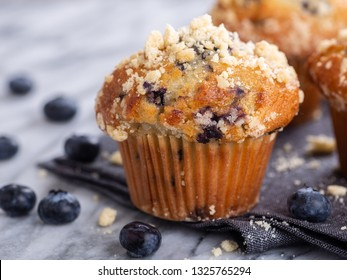 Closeup of a blueberry muffin on a napkin with blueberries and muffins in background