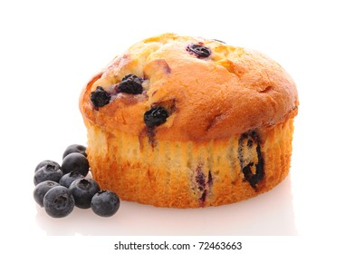Closeup of a Blueberry Muffin on a white surface with loose berries. Horizontal format with reflection.