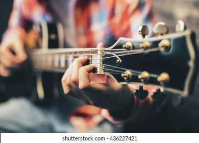 Closeup of blurry male hands playing the guitar