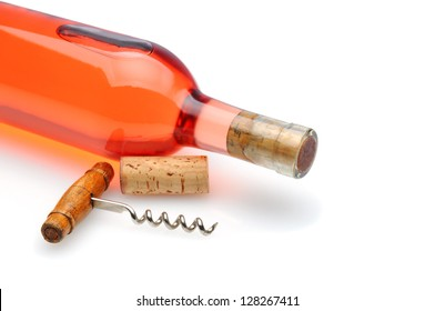 Closeup of a blush wine bottle and corkscrew laying on a white background with reflection and shadow.