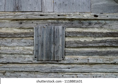 Close-up of a boarded up window on a weathered log cabin