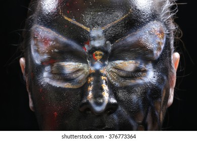 close-up body art - butterfly Totenkopf on the girl's face on a black background Studio