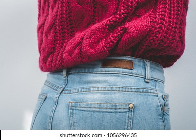 Close-up body part of woman dressed in a knitted large viscous pink sweater tucked into blue jeans. Back view.