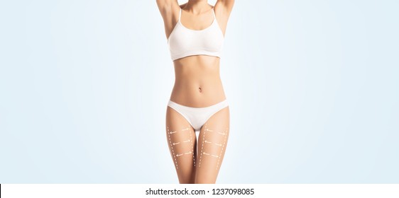 Close-up body of a young, fit and sporty female body in white underwear. Skincare, fitness, dieting, fat loss concept.