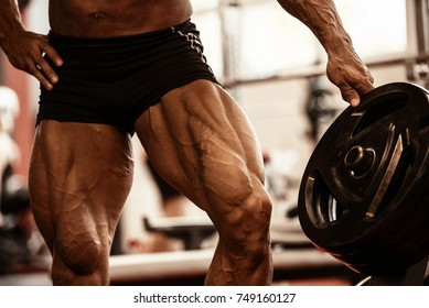 Close-up of bodybuilders muscular legs. Athlete man doing workout exercise in gym