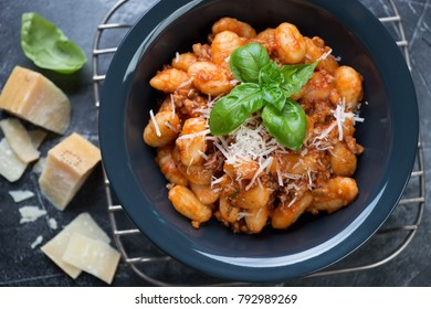 Close-up of boiled potato gnocchi served in a plate with meat sauce and cheese, view from above