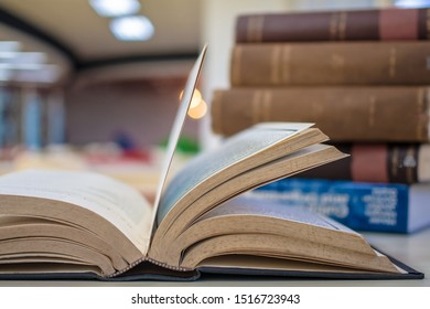 Close-up book in library, open old text book and stack of literature texts, with the hidden light from background. For academic education learning concept.