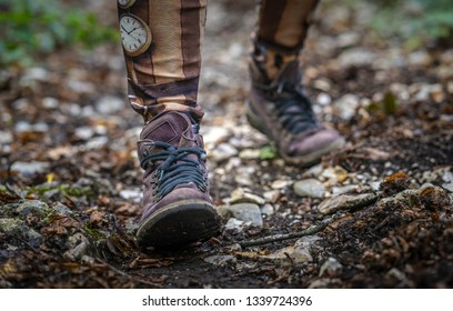 Close-up of the boots of a person walking on the forest path
