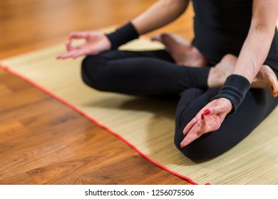 Closeup of Both Hands of Caucasian Brunette Woman Practicing Yoga Indoors. Doing Sukhasana Exercises In Lotus Pose. In Front of Sunny Window in Background.Horizontal Image