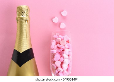 Closeup of a bottle of champagne and a flute filled with pink candy hearts for Valentines Day. On a pink background with copy space.