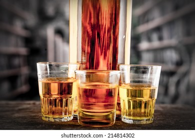 Closeup of Bottle and glass shots with yellow liqour resembling whiskey, rum, tequila, spirit on wooden table