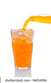 Closeup of a bottle of Orange Soda Pouring into Glass of Ice. Vertical format over a white background with reflection.