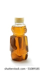Closeup of a bottle shaped like a bear and filled with honey ... isolated on white background