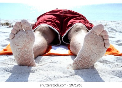 Closeup of bottom of feet on beach with sand sticking to them