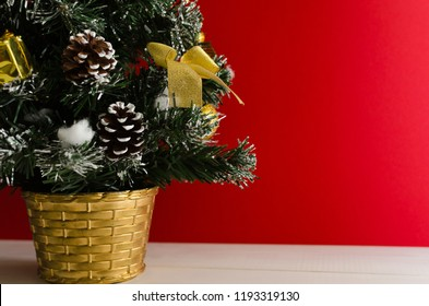 Close-up. Bottom part of a christmas tree decorated with golden ornaments stands on a white wooden table in front of a red background