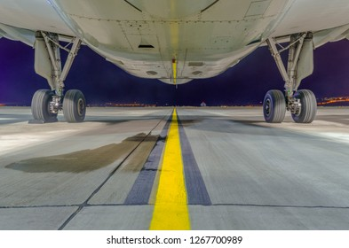Close-up and bottom view of Airbus A320-232 aircraft's fuselage and main landing gear at night. Tbilisi International Airport, Tbilisi, Georgia