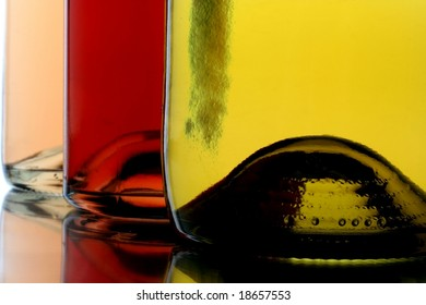 Closeup of bottoms of three different colored wine bottles.