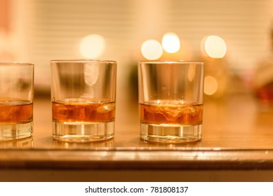 closeup of bourbon whiskey glasses with ice lined up on wood table with candles in background