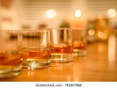 closeup of bourbon whiskey glasses on the rocks lined up on wood table with candles in background