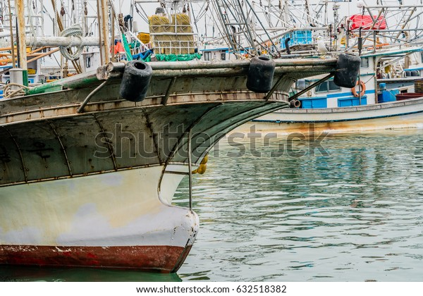 Closeup of bow of large fishing vessel anchored in harbor with other boats and rigging in the background